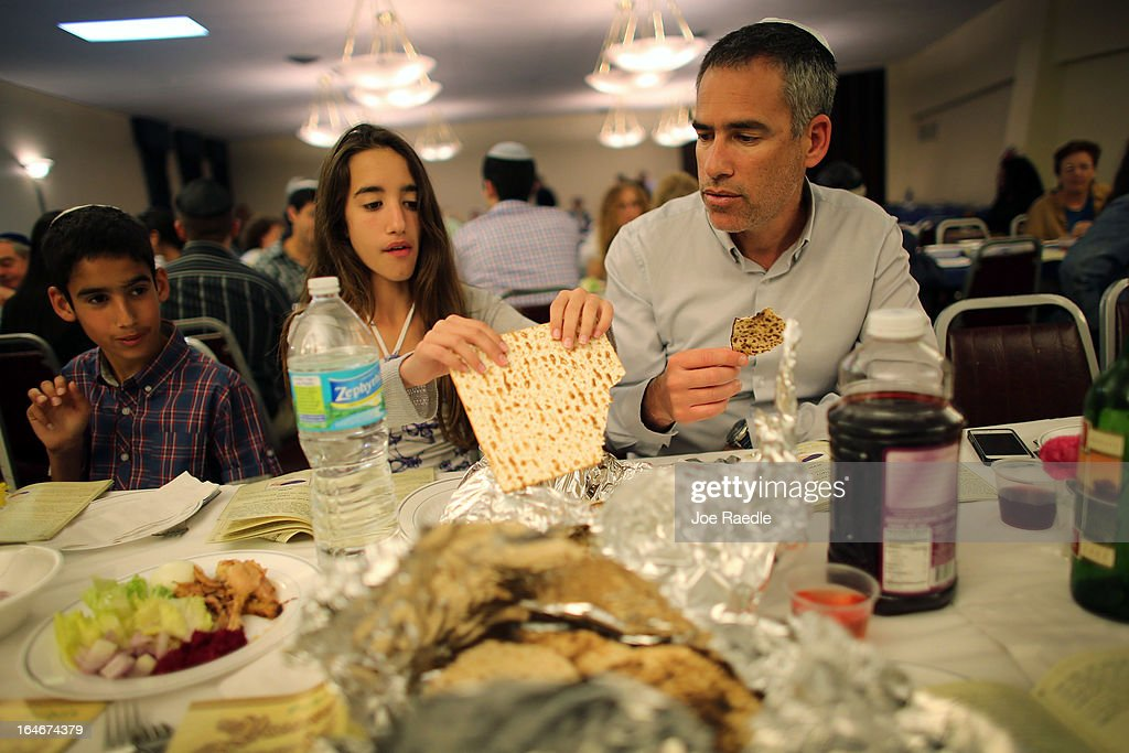 Omri Brandes, Nitzan Brandes and Bentsi Brandes eat matzo during a community Passover Seder at Beth Israel synagogue on March 25, 2013 in Miami Beach, Florida. The community Passover Seder that served around 150 people has been held for the past 30 years and is welcome to anyone in the community that wants to commemorate the emancipation of the Israelites from slavery in ancient Egypt.