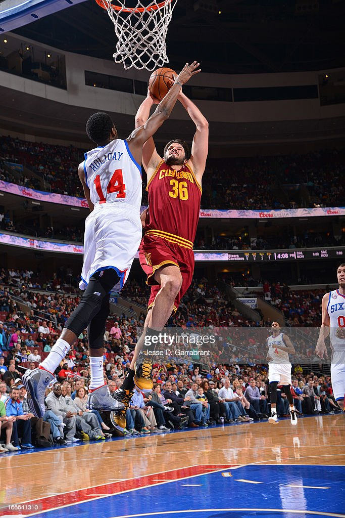 Omri Casspi #36 of the Cleveland Cavaliers shoots a layup against Justin Holiday #14 of the Philadelphia 76ers at the Wells Fargo Center on April 14, 2013 in Philadelphia, Pennsylvania.