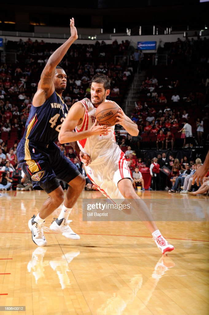Omri Casspi #18 of the Houston Rockets drives the ball against Lance Thomas #42 of the New Orleans Pelicans during the 2013 NBA pre-season game on October 5, 2013 at the Toyota Center in Houston, Texas.