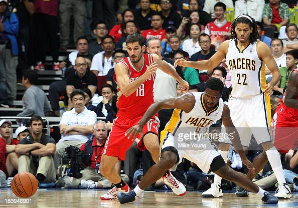 Omri Casspi of the Houston Rockets reacts after Solomon Hill loses the ball as Chris Copeland of the Indiana Pacers looks on during the NBA game at...