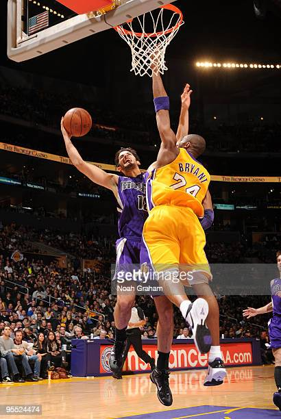 Omri Casspi of the Sacramento Kings avoids contact from Kobe Bryant of the Los Angeles Lakers while attempting a shot during their game at Staples...