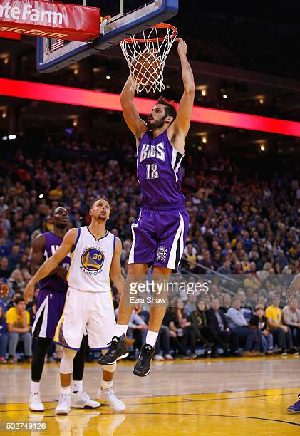 Omri Casspi of the Sacramento Kings dunks the ball over Stephen Curry of the Golden State Warriors at ORACLE Arena on December 28 2015 in Oakland...