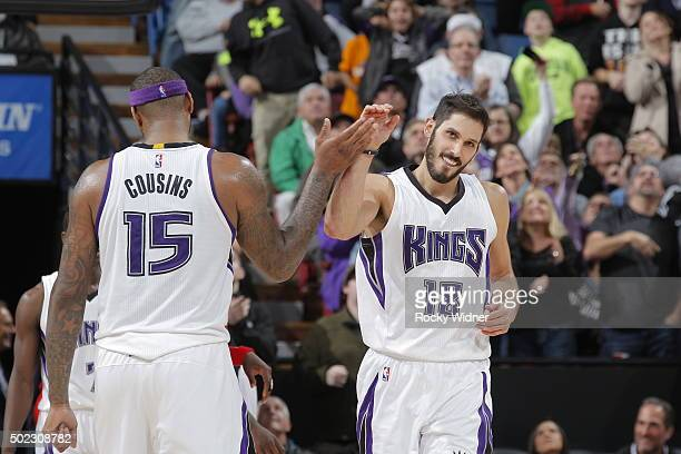 Omri Casspi of the Sacramento Kings high fives teammate DeMarcus Cousins against the Houston Rockets on December 15 2015 at Sleep Train Arena in...