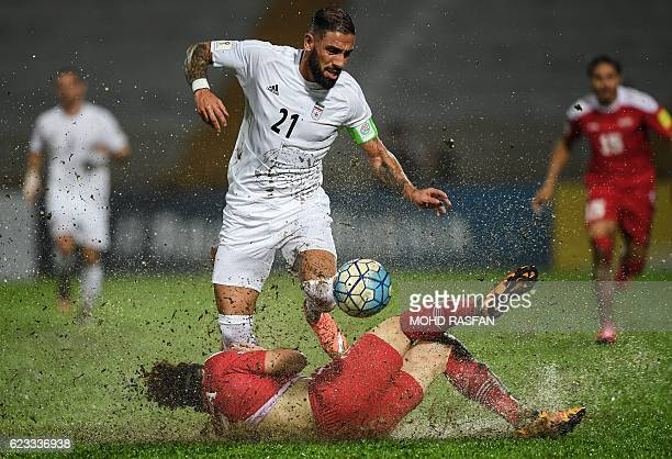 TOPSHOT Omro Al Midani of Syria fights for the ball with Ashkan Dejagah of Iran during the 2018 World Cup qualifying football match between Syria and...