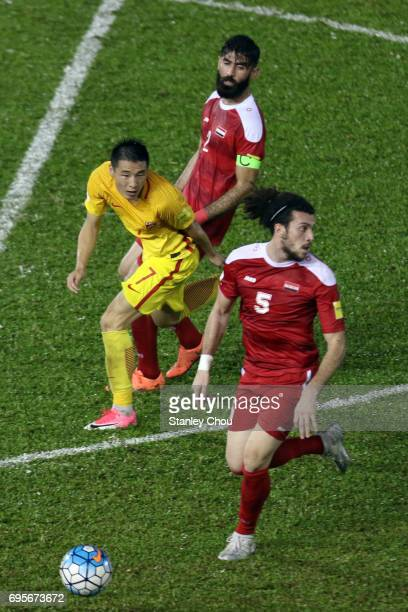 Omro AL Midani of Syria holds off Wu Lei of China during the 2018 FIFA World Cup Asian Qualifier Group A Final Round match between Syria and China at...