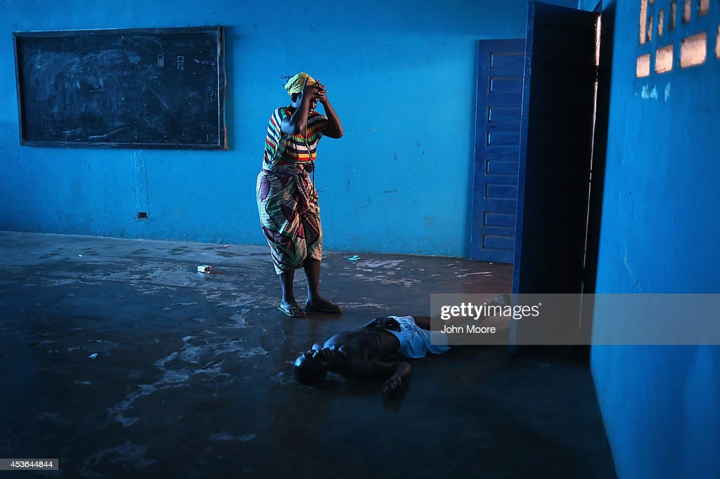 Omu Fahnbulleh stands over her husband Ibrahim after he staggered and fell knocking him unconscious in an Ebola ward on August 15 2014 in Monrovia...