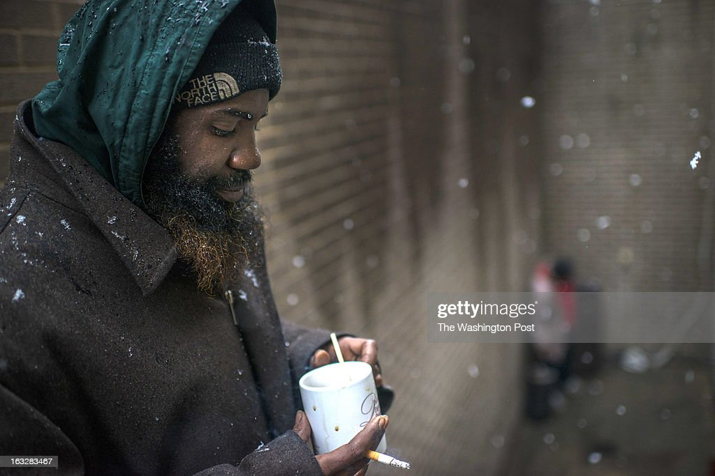On a chilly, wet and snowy morning Karim Elamin, homeless and father of two smokes and drinks a cup of coffee, on the steps leading to Miriam's Kitchen serving the homeless and needy community no matter the weather in Washington DC on Wednesday March 6, 2013.