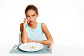 Portrait of sad girl looking at camera with peas and leeks on plate in front