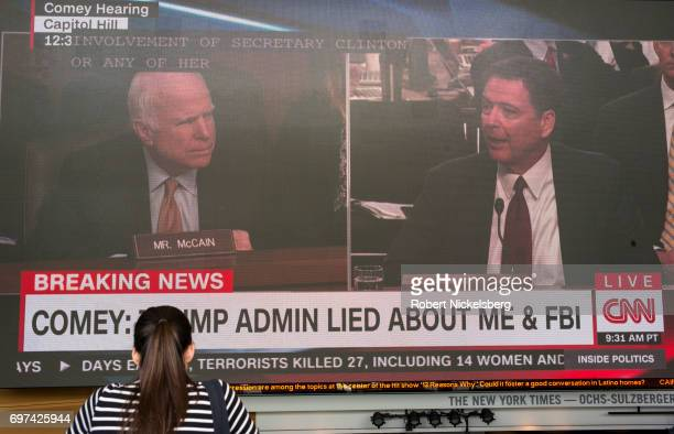 On a large television screen US Senator John McCain left questions former FBI Director James Comey right during Comey's testimony June 8 2017 in...