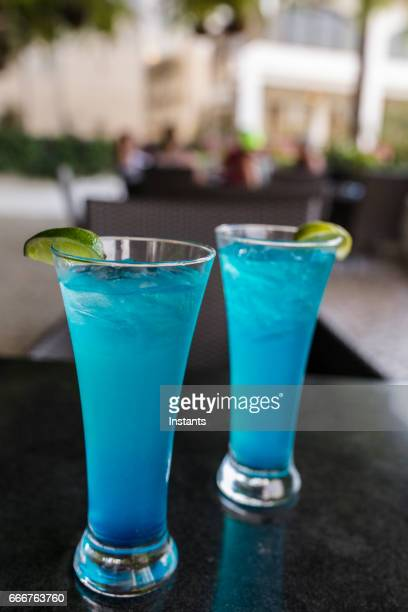 On a Panama City terrace, two refreshing Blue hurricane cocktails made with rum, Curacao, orange and pineapple juices with a lime wedge and lots of ice cubes.