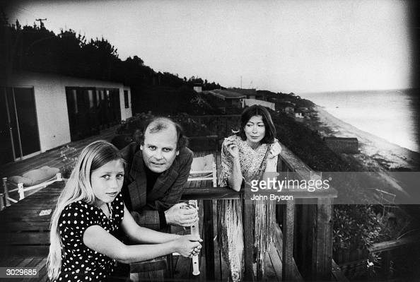 On a patio deck overlooking the ocean Quintana Roo Dunne leans on a railing with her parents American authors and scriptwriters John Gregory Dunne...