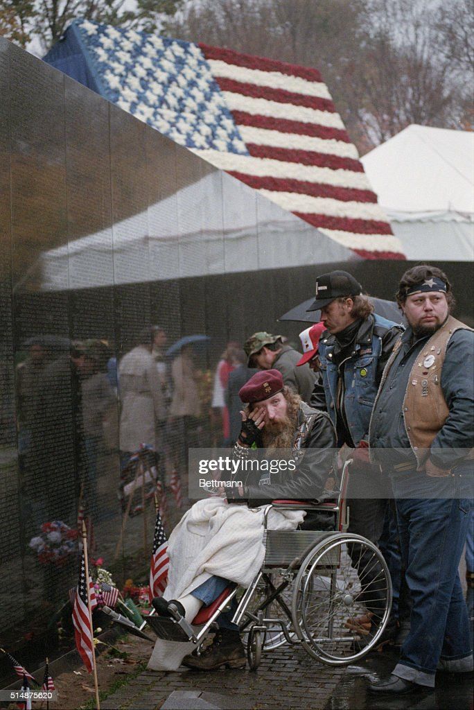 On a rainy Veterans Day in DC, this wheelchair-bound veteran breaks down as he and others pay their respects to those who died in Vietnam; behind the Vietnam Memorial is a flag made of 58,000 flowers.