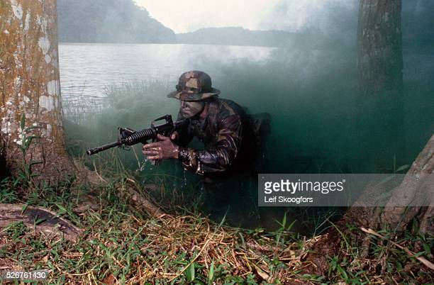 On a special operation with a SBU Navy SEAL CL Martin lands on the shore of a river aiming a M16A3 rifle He is camouflaged by a cloud of green smoke