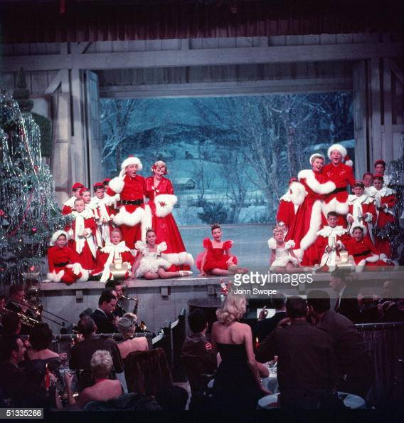 On a stage full of children American actors Bing Crosby Rosemary Clooney VeraEllen and Danny Kaye perform on stage dressed in red outfits with white...