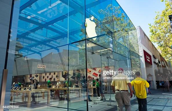 On a sunny day two menone wearing a Stanford University baseball capwalk past the entrance to the flagship Apple electronics store on University...