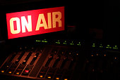On Air sign in a studio broadcasting via radio, podcast or wireless transmission.  The only light source is the glow from the on air sign.  This is the true color of a broadcast studio sign.On air, on