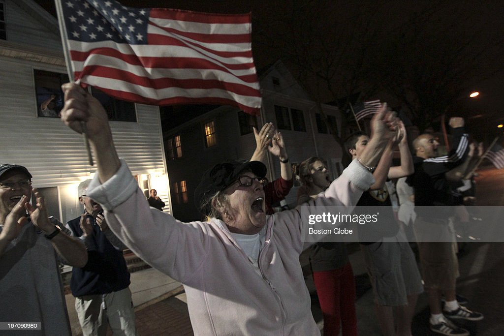 On Arsenal Street, Louise Hunter and others cheer on police on leaving the scene. After an intense manhunt and two-hour standoff in Watertown, law enforcement took a person into custody believed to be related to the Boston Marathon bombings.