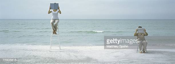 On beach, man and woman sitting holding up reading material in front of faces
