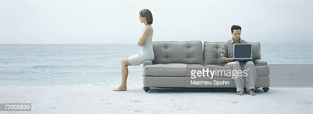 On beach, man using laptop on sofa while woman turns back to him