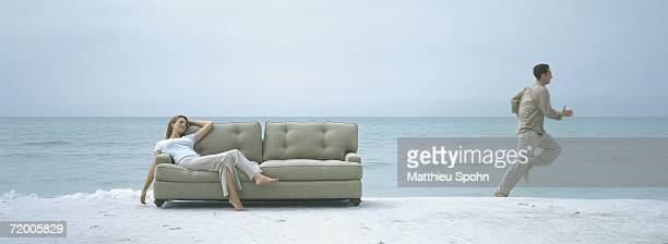 On beach, woman reclining on sofa while man runs away