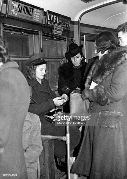 On board a tram a young woman wearing the uniform of a ticket inspector of ATM checking the tickets of some passengers Milan 1950s