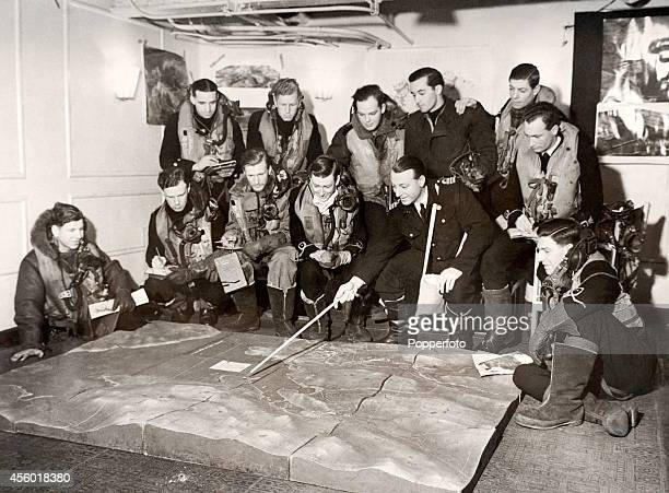 Commander S T C Harrison with the aid of a relief map briefs crews who will take part in the Fleet Air Arm attack on the German battleship Tirpitz in...