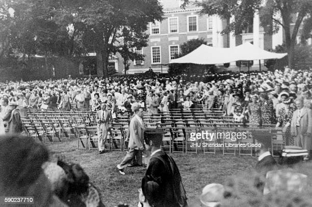 On Commencement Day a crowd of parents and guests stand outside behind chairs lined up in rows on the quadrangle in front of Gilman Hall a humanities...