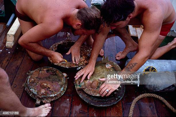 On deck a trio of divers examine several rusted artifacts retrieved near Cocos Island off the coast of Costa Rica 1964