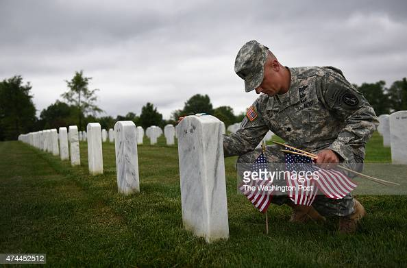 On FlagsIn Day Army Lt Col Michael B Baka places remembers a fellow soldier Raymond Ross Powell at Arlington National Cemetery in Arlington VA on May...
