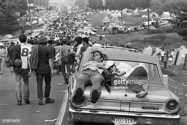 On foot in cars atop cars young people leave the great lovein of the sixties the Woodstock Music Festival Three hundred thousand young people...