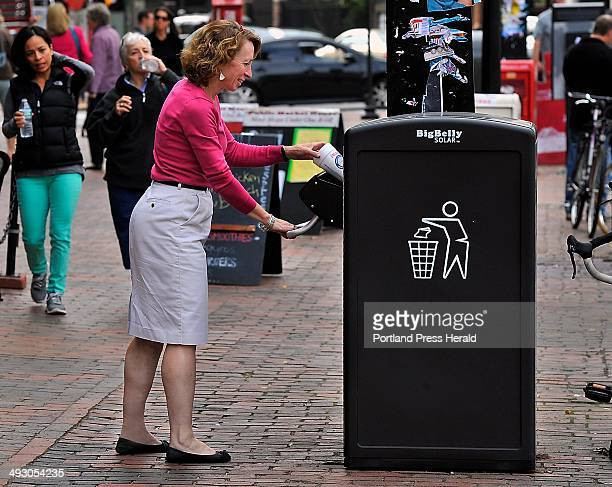 On Friday October 11 Kimberly Mills of Brunswick tosses trash into the new solar powered trash compactor in Monument Square
