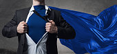 Young businessman dressed as superhero against concrete background
