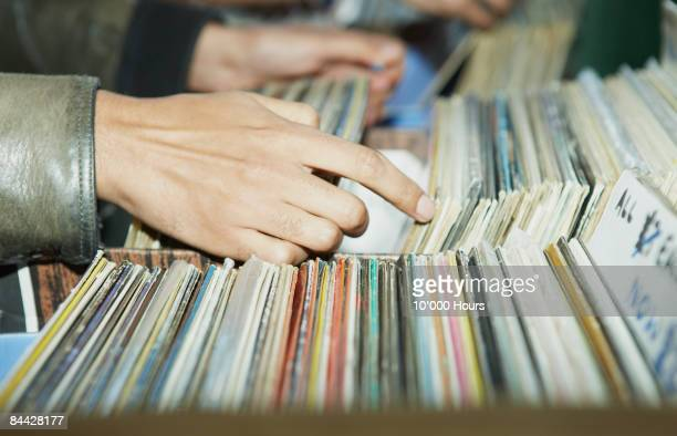 CU on hands searching through vintage records