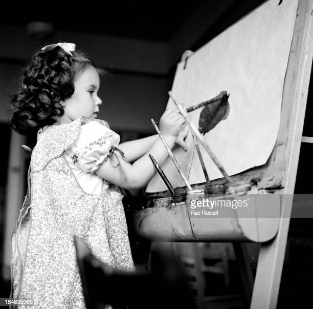 On her first day of nursery school a young girl paints at an easel during an art class Madison New Jersey 1948 The picture was taken for a magazine...