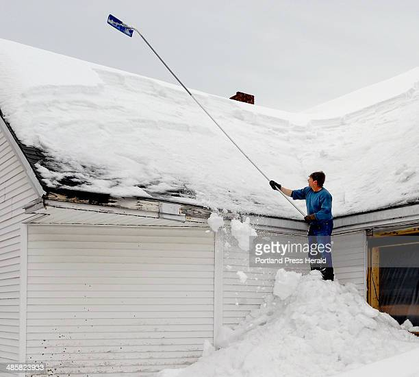 PHOTOGRAPHER On March 4 2008 Herb Libby of Raymond stands on a pile of snow he already removed as he rakes snow off the roof of Windham home owner...