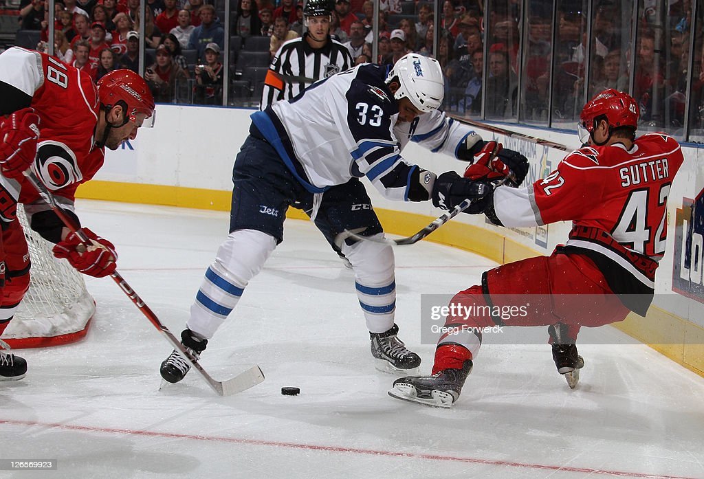 on Matsumoto #18 of the Carolina Hurricanes picks up the loose puck as teammate Brett Sutter #42 battles against <a gi-track='captionPersonalityLinkClicked' href=/galleries/search?phrase=Dustin+Byfuglien&family=editorial&specificpeople=672505 ng-click='$event.stopPropagation()'>Dustin Byfuglien</a> #33 of the Winnipeg Jets during an NHL preseason game on September 25, 2011 at Time Warner Arena in Charlotte, North Carolina.
