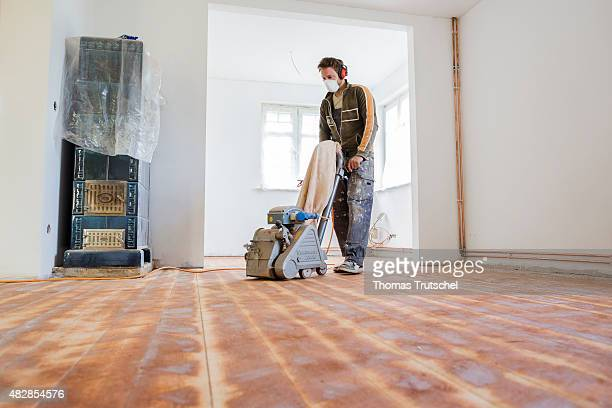 A man drags a grinder from wood planks in an old house that he is renovating