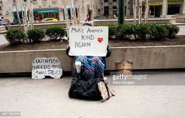 On Michigan Avenue an unidentified panhandler holds up a sign that reads 'Make America Kind Again' Chicago Illinois February 25 2017 The sign is a...