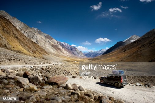 Suv On Mountain Dirt Road Camping Gears On Roof Stock Photo