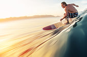 Surfer rides the perfect ocean wave at sunrise. Motion blurred water