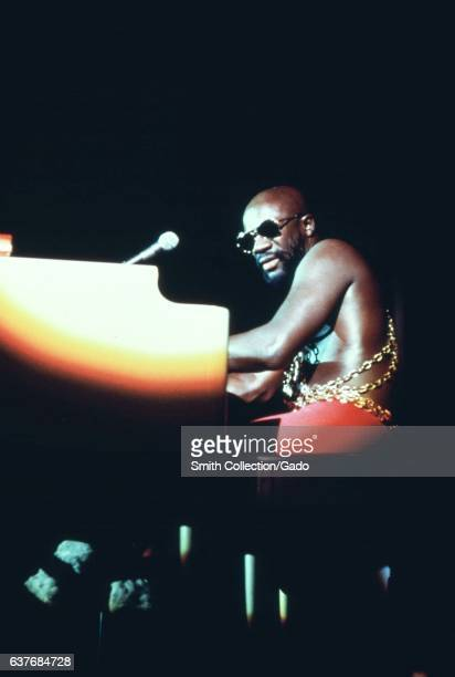 On stage during an annual Black Talent Expo soul singer Isaac Hayes reaches his hands across the keys of a large piano reflecting the glow from the...