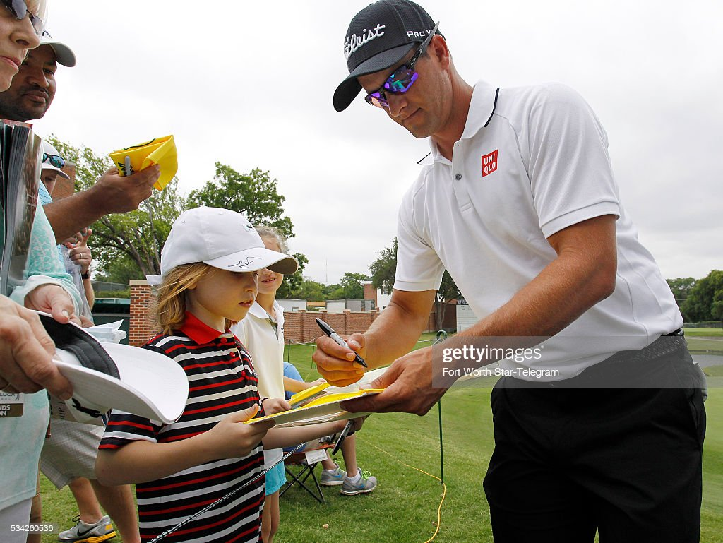 On the 16th green, 2014 tournament winner Adam Scott signs a flag for Alex Wimmiams during the Colonial Pro-Am at the Dean & Deluca Invitational on Wednesday, May 25, 2016, in Fort Worth, Texas.