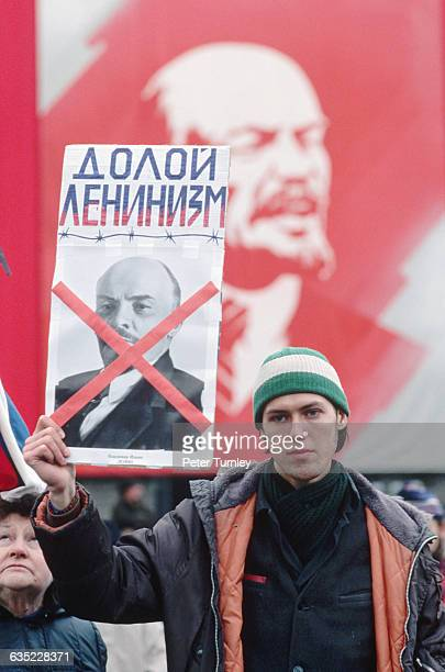 On the 73rd anniversary of the Russian Revolution a protester holds up a card reading 'Down with Leninism' in Russian