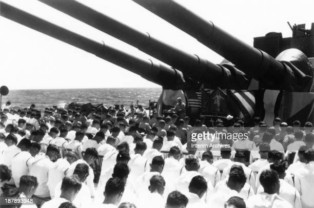 On the American battleship USS South Dakota the crew bows their heads as Chaplain Lindner reads a benediction in honor of sailors killed in action...