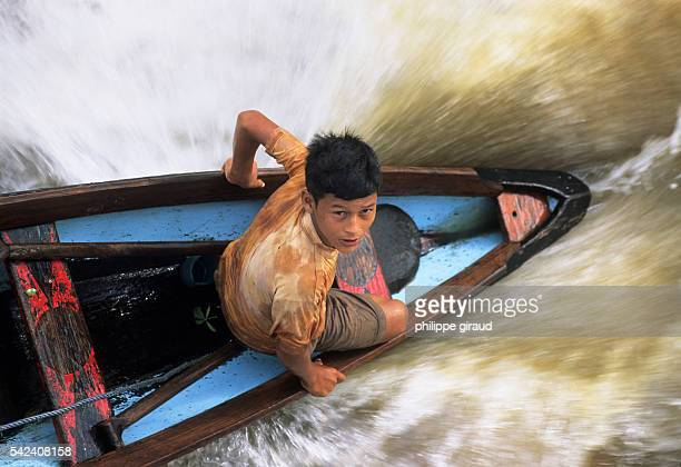 On the banks of the Amazon reckless fruit and shrimp sellers hang on to passenger boats during their crossing of the river mouth from Belem to earn a...