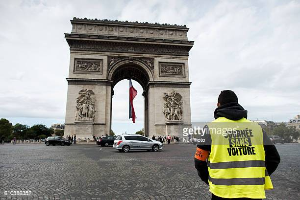 On the Champs Elysées during the 2016 carfree day that Paris organises in over 45% of the area of the city a man in front of the Triumph Arch wears a...