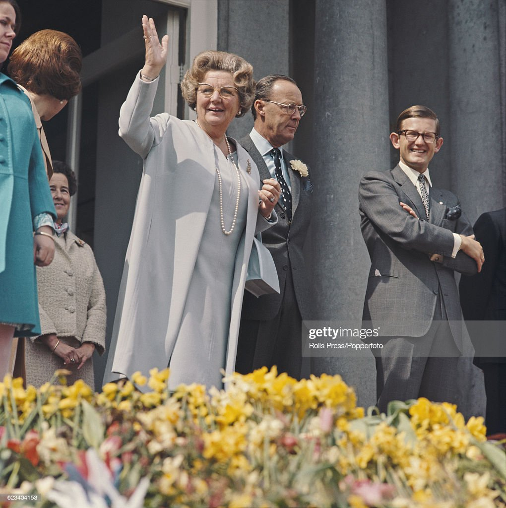 On the day of her 60th birthday, Queen Juliana of the Netherlands (1909-2004) waves to crowds of spectators along with Prince Bernhard of Lippe-Biesterfeld (1911-2004) and Pieter van Vollenhoven (right), from a balcony at the Soestdijk Palace in Utrecht, Netherlands on 30th April 1969.