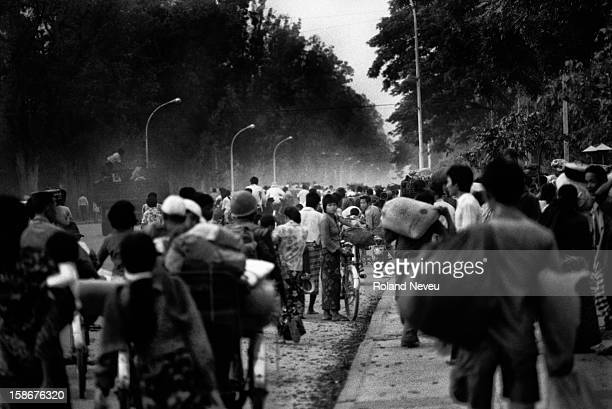On the eve of the Fall of Phnom Penh to the Khmer Rouge on April 16 1975 as night fall thousands of people are streaming towards the center of Phnom...