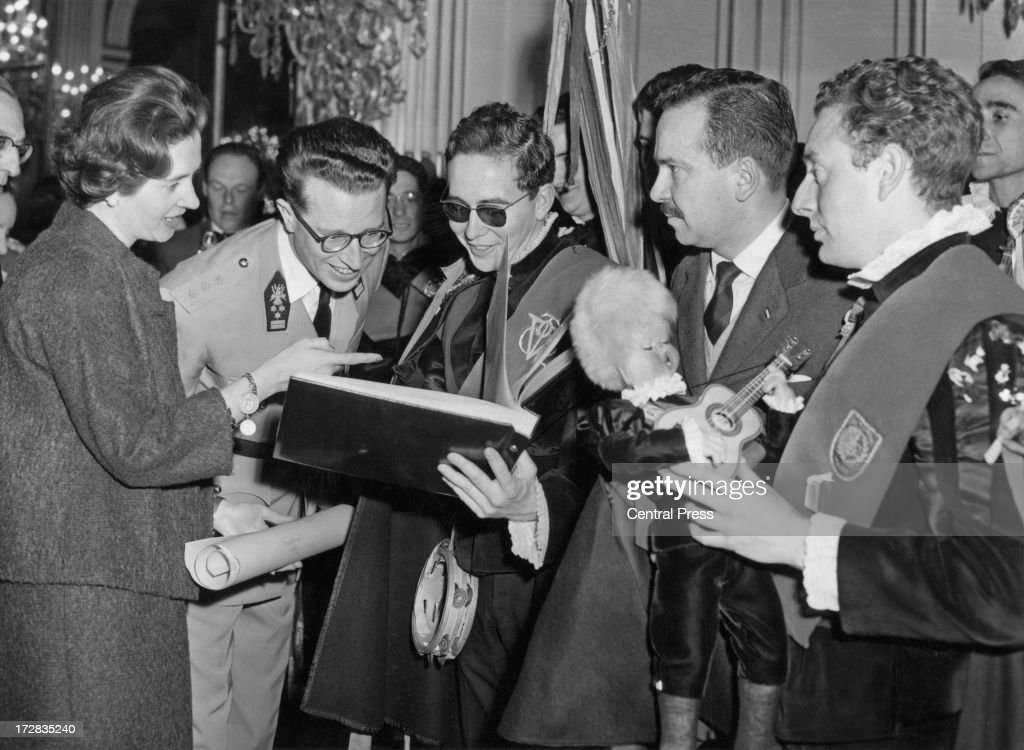 On the eve of their wedding day, King Baudouin of Belgium (1930 - 1993) and Queen Fabiola of Belgium are presented with an album of photo's by students from the University of Madrid at the Palace of Brussels, 14th December 1960.