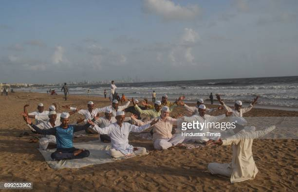 On the eve of World Yoga Day Mumbai's Dabbawala celebrate the day by doing yoga exercises at Versova beach on June 20 2017 in Mumbai India...